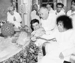 Sathya Sai Baba. 84th Birthday. Aide helps him to cut cake